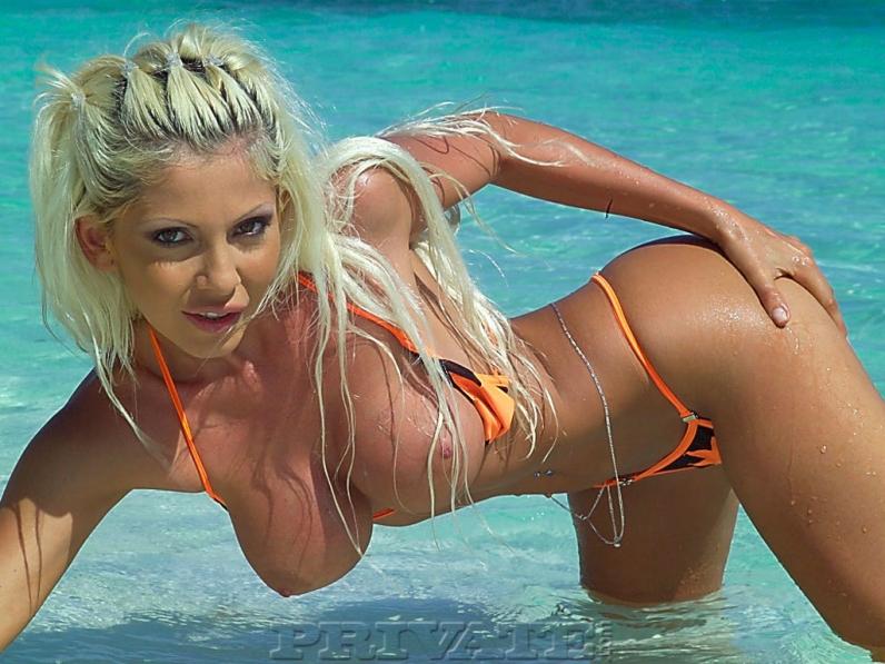 Девушка в бикини эротично раздевается в море