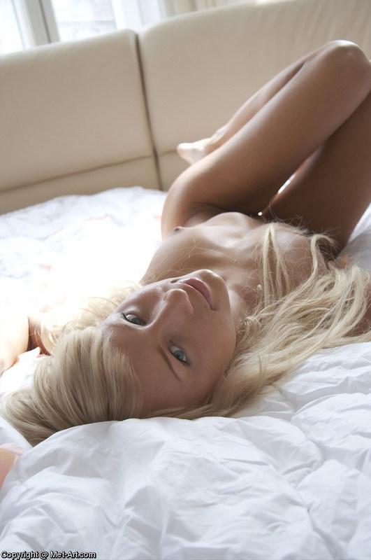 Нагая красотка модель со свелыми волосами в постели из лепестков роз секс фото