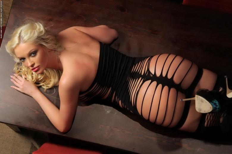 Дама на столе в сексуальном белье на крупных сиськах и длинных ногах