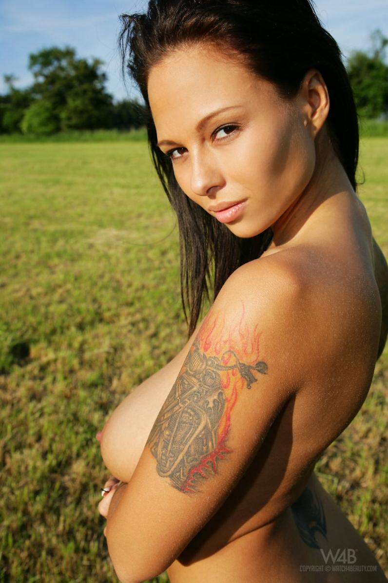 Девка с изящной фигурой с татуировками на природе щеголяет роскошной жопой