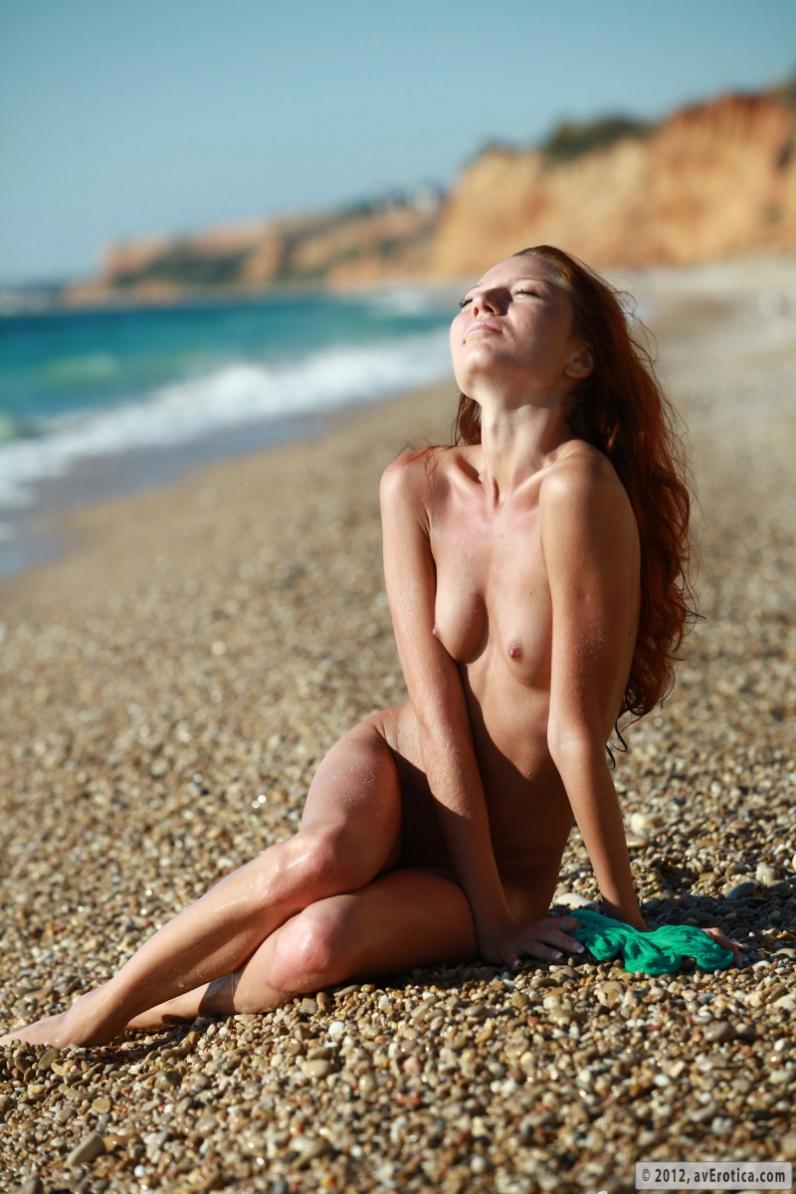 Каменистый пляж с раздетой рыжей чувихой в голубых волнах