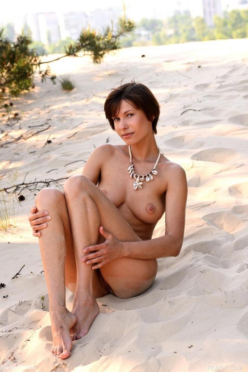 Зрелая фрау с прекрасными ногами раком ползет по песку заманчиво покачивая маленькой попой