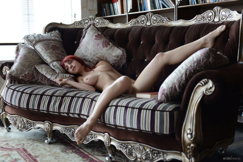 Рыженькая тетка без одежды на козетке читает книжку