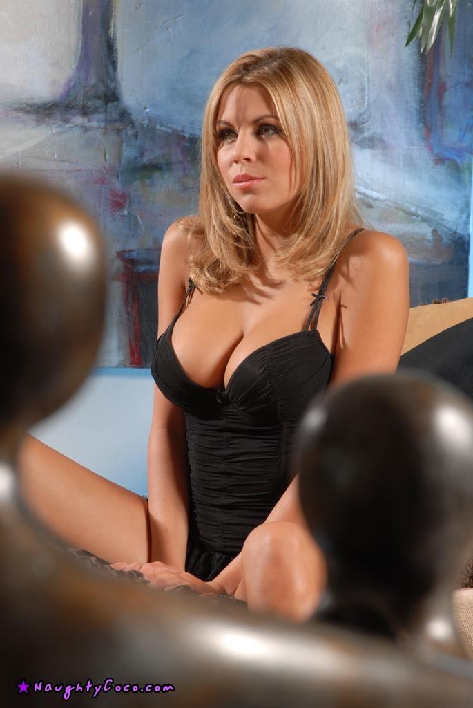 Красивая блондинка с огромными сиськами мастурбирует лежа