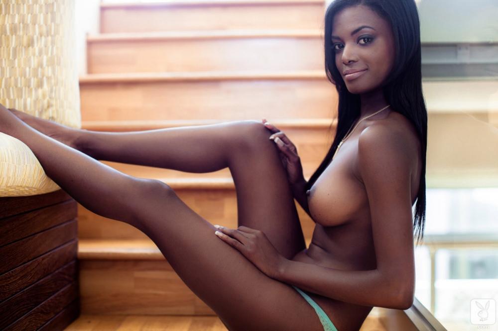 Шоколадная красотка обнажает на фото сахарные дойки и попу под голубым бикини секс фото