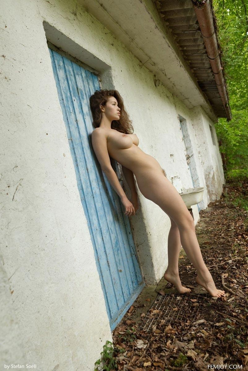 Свежая фотомодель без одежды на поляне с небритой киской и крепкими естественными дойками