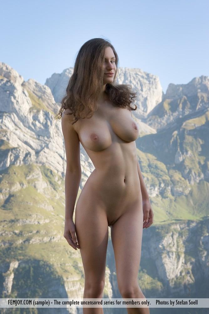 На вершине горы раздетая фотомодель делает селфи шикарными дойками и выбритой киской