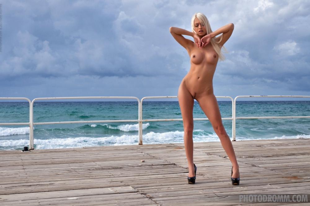 Красивая блондинка в бикини снимает трусы на пляже