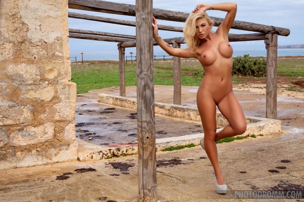 Подтянутая блондинка Brigitta на открытом воздухе снимает лифчик до гола снимая обтягивающее сексуальную фигуру и большие сиськи сексуальное белье