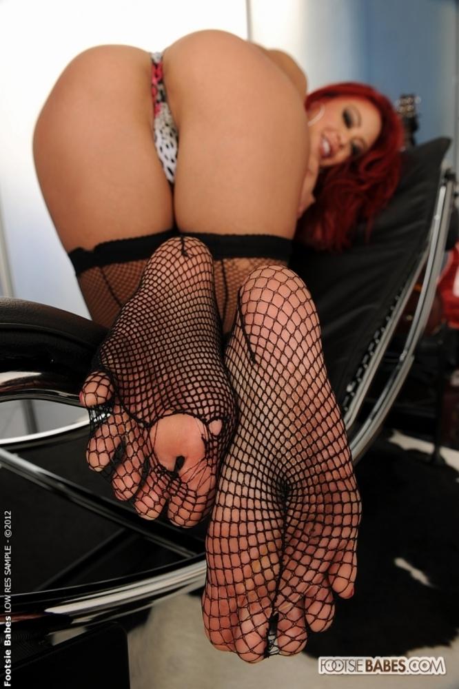 Рыжая проститутка в чёрных чулках секс-фото